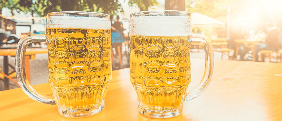 Werbeartikel für den Biergarten. Zwei Maßkrüge im Biergarten auf dem Tisch