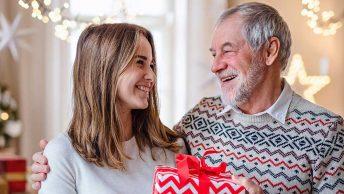 Zwei Personen halten ein Geschenk in der Hand und stehen in einem weihnachtlich dekorierten Zimmer mit Weihnachtsbaum. Die beiden schauen sehr glücklich, da sie nicht in Weihnachtsstress verfallen sind.